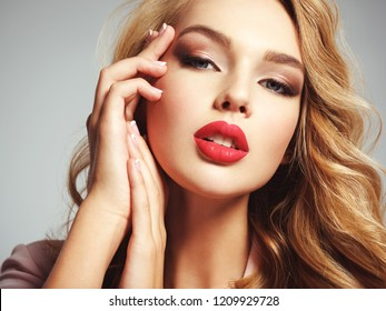 Photo of a beautiful young blond girl with sexy red lips. Closeup attractive sensual face of white woman with long curly hair.