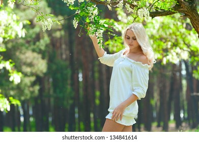 photo of a beautiful young blonde posing on a background of the spring woods