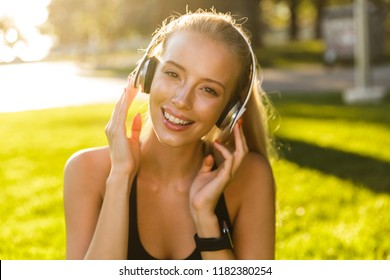 Photo of beautiful young blonde sports woman in park outdoors listening music with headphones.