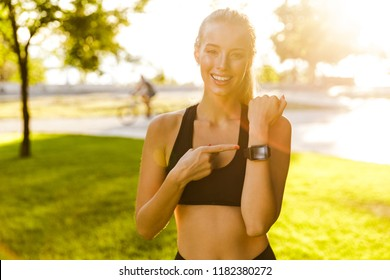 Photo of beautiful young blonde sports woman in park outdoors showing watch clock.