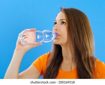 Photo of a beautiful young brunette woman drinking bottled water over blue background.
