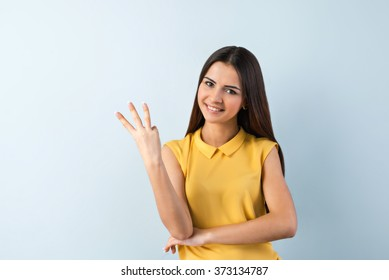 Photo of beautiful young business woman standing near gray background. Smiling woman with yellow shirt looking at camera and showing three fingers