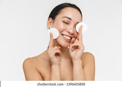 Photo of a beautiful young pretty asian woman with healthy skin posing naked isolated over white wall background holding cotton pads.