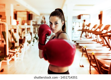 Photo of beautiful young woman boxing at gym.