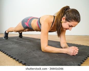 Photo of a beautiful young woman exercising and doing an elbow plank to strengthen her stomach muscles.