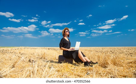photo of the beautiful young woman sitting on the suitcase with laptop in the field