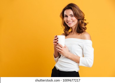 Photo of beautiful young woman standing isolated over yellow background. Looking camera drinking tea.