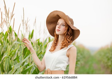 photo of beautiful young woman standing near the wheat plant