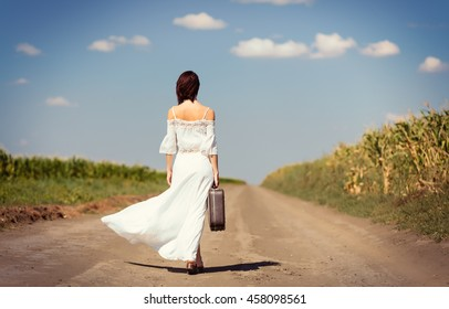 photo of the beautiful young woman with suitcase  walking on the road