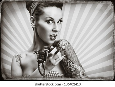 Photo of beautifull pin-up girl with tattoos and tattoo machine tattoing herself and looking at the camera