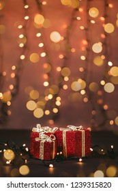 Photo of a beautifully wrapped presents with yellow Christmas bokeh lights