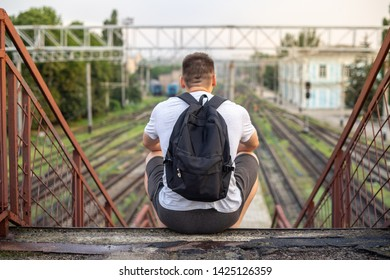 photo from behind young man with bag sitting on empty train station