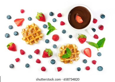 A photo of Belgian waffles with fresh fruit, mint leaves, and a cup of hot chocolate, shot from above on a white background