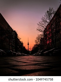 Photo of the Berlin TV tower on the background. Leading lines going towards the TV tower and the sunrise sky on the background.