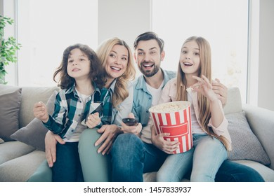 Photo of big family four members excited by watching tv show sit couch eat salty popcorn