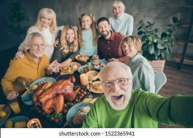 Photo of big family sit hugging feast dishes table around roasted turkey multi-generation relatives grey-haired grandpa making group selfies in living room indoors