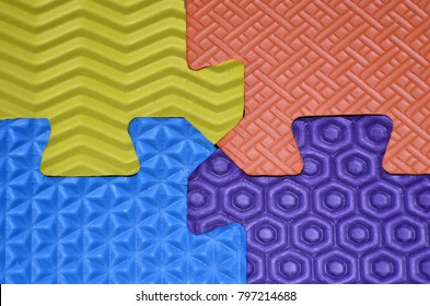 Photo of big four pieces of puzzles - yellow,orange, blue, purple with different geometric seamless shapes pattern. Puzzle Color Rubber Floor