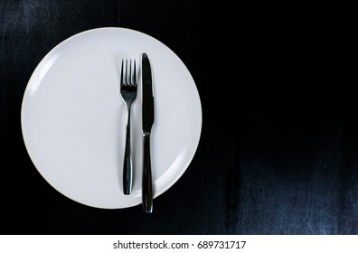photo  Big white dish Black back , Steak knife and spoon  On the black background
