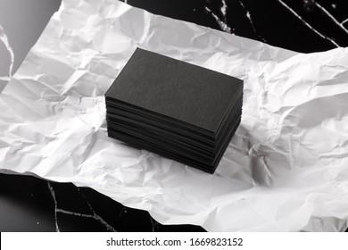 Foto von schwarzen Visitenkarten auf schwarzem Marmor auf weißem zerkleinertem Papier. Vorlage für die Markenidentität einzeln auf Marmor-Hintergrund. Visitenkarte einzeln auf Marmorstein.