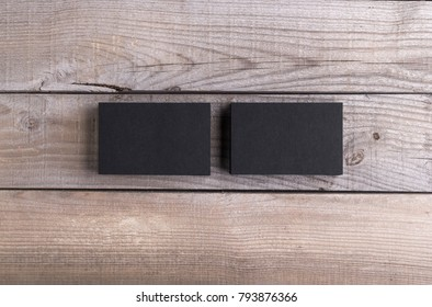 Photo of black business cards. Template isolated on old wood background. For graphic designers presentations and portfolios damaged weathered antique mock-up with black business cards