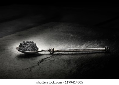 A photo of black caviar in a spoon, on a black background with copyspace