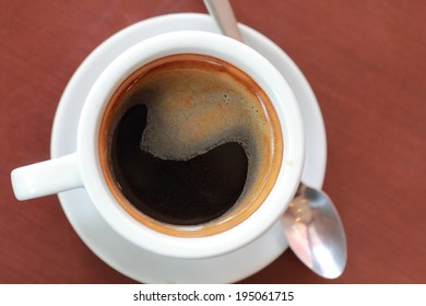 a photo of black coffee in white mug on table