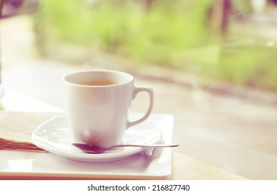 a photo of black coffee in white mug on table with texture