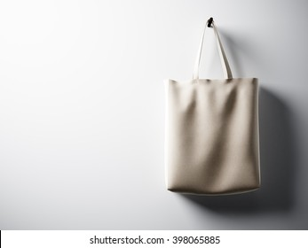 Photo black cotton textile bag hanging in right side. Empty white wall background. Highly detailed texture, space for business message.  Horizontal. 3D rendering