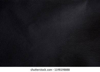 Photo of black leather texture with light irregularities for material background.
