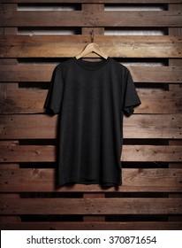 Photo of black tshirt holding on wood background