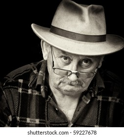 photo black and white portrait  of senior old elderly pensioner man male with sad depressed grumpy close up face portrait wearing fedora hat.