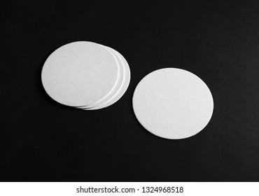 Photo of blank beer coasters on black paper background.