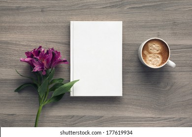 Photo blank book cover on textured wood background with spring flower and cape of coffee