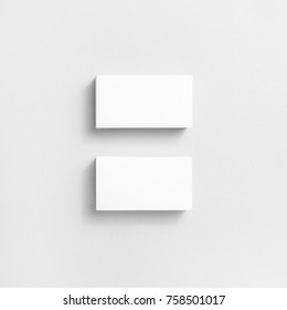 Photo of blank business cards with soft shadows on paper background. For design presentations and portfolios. Top view.