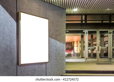 Photo blank mockup of event poster lightbox  glowing on concrete wall at night