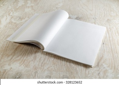 Photo of blank opened brochure magazine on wooden background with soft shadows. Mock-up for graphic designers portfolios.