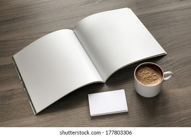Photo blank set. Open square format brochure, b-card and cup of coffee on a wooden table