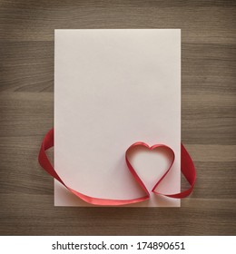 Photo blank sheet, ribbon with heart on textured wood background