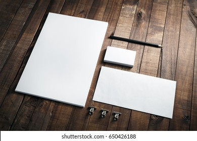 Photo of blank stationery set on wood background. Envelope, business cards, pencil, and A4 paper. Corporate identity template. Responsive design mockup.