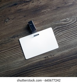 Photo of blank white plastic badge on wood table background. Blank id card. Template for your design. Top view.