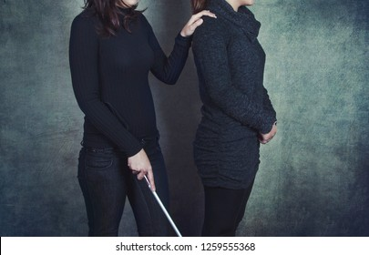 Photo of a blind woman and her personal assistant as a symbol of support