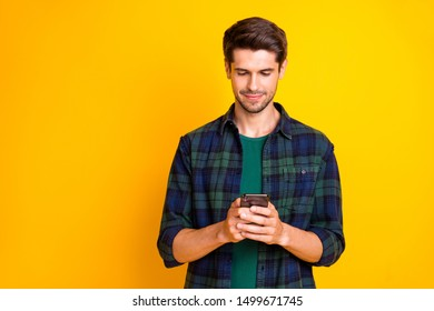 Photo of blogger guy holding telephone in hands checking instagram followers wear casual checkered shirt isolated yellow color background