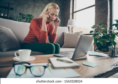 Photo of blond business lady tired hard-working holding temples suffering terrible migraine wear specs orange pullover sitting sofa table notebook diary coffee indoors