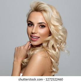 Photo of blond female model with white teeth looking at camera and smiling