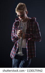 Photo of the blond teenager in checkered shirt and sunglasses playing jazz on trumpet in front of dark blue background