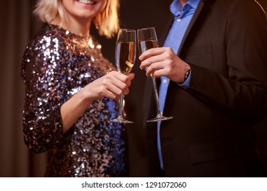 Photo of blonde woman in brilliant dress and men with wine glasses with champagne on black background