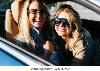 Photo of blondes wearing sunglasses while driving in car