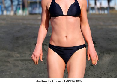 Photo of a body part in a swimsuit on the beach on a Sunny day. The is relaxing on the beach.