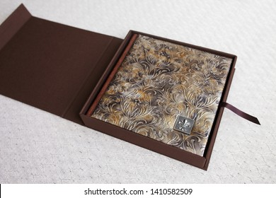 Photo book with a cover of genuine leather in the box. Brown color with decorative stamping. Opening box with photoalbum