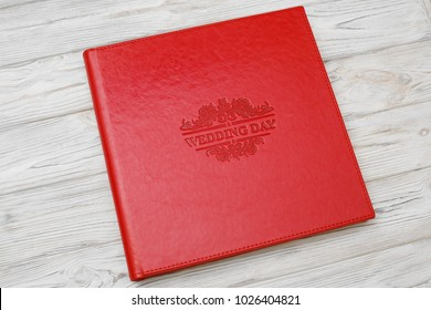 Photo book with embossing. Photo book on a light surface. Red photo book with  leather cover. Photoalbum with a hard cover on a wooden background. Bright red photo album.
